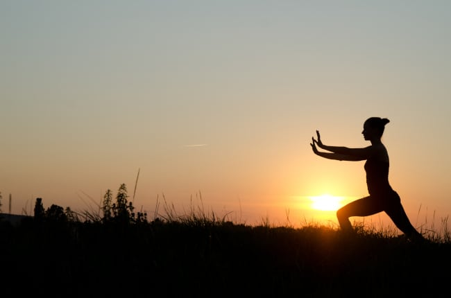 A lady doing a tai chi in front of a sunset