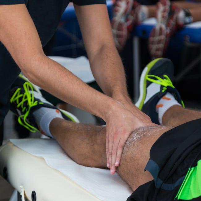 A masseur doing a massage on the left upper knee of an athlete