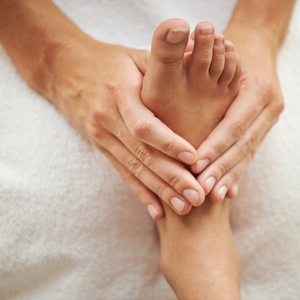 A hand of a massage therapist doing a reflexology massage to the right foot