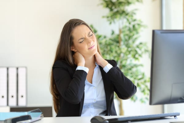A woman in the office having a neck pain