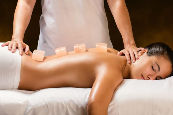 A woman laying on a bed and having a Himalayan hot stone massage