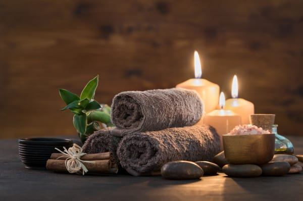 A table with a candle light a cup of salt , herbal flower, stone and a towel