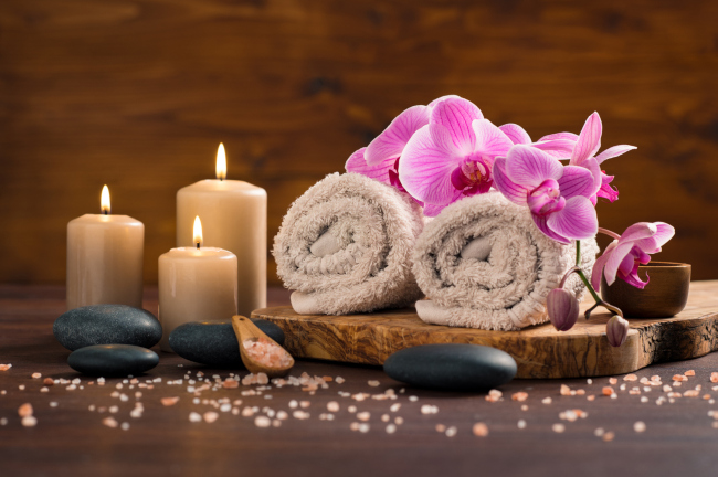 A massage wood tray with a massage towels, candles a massage stones a cup and an orchid