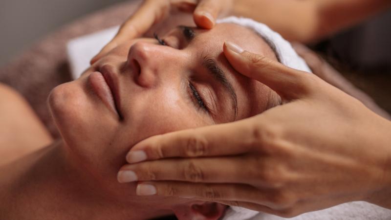 A face of a woman having a Facial Massage