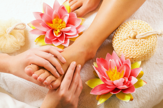 A left foot of a lady placed on a white towel with a herbal flower and a sponge