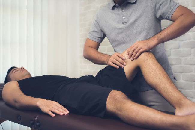 An athlete having a sports massage on his knee