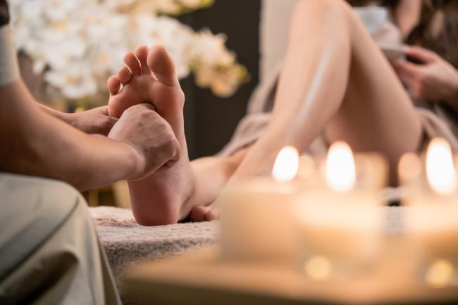 A massage therapist doing a reflexology massage to a lady