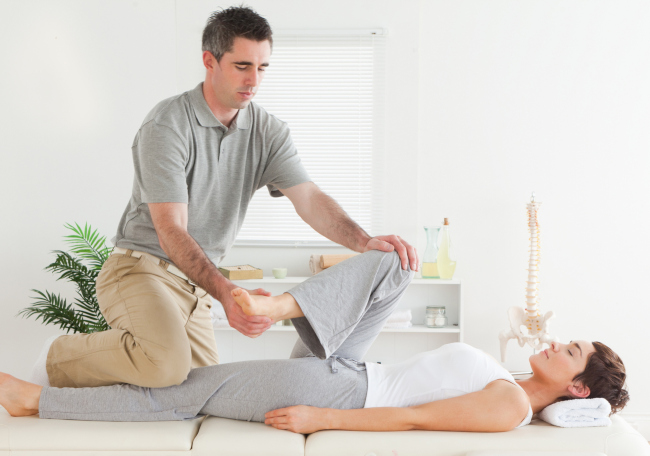 A masseur doing a stretching massage to a woman