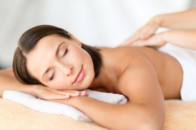 A lady having a massage therapy on the bed