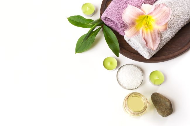 A massage wood tray with towels a candles a herbal flower a massage stone and massage oil