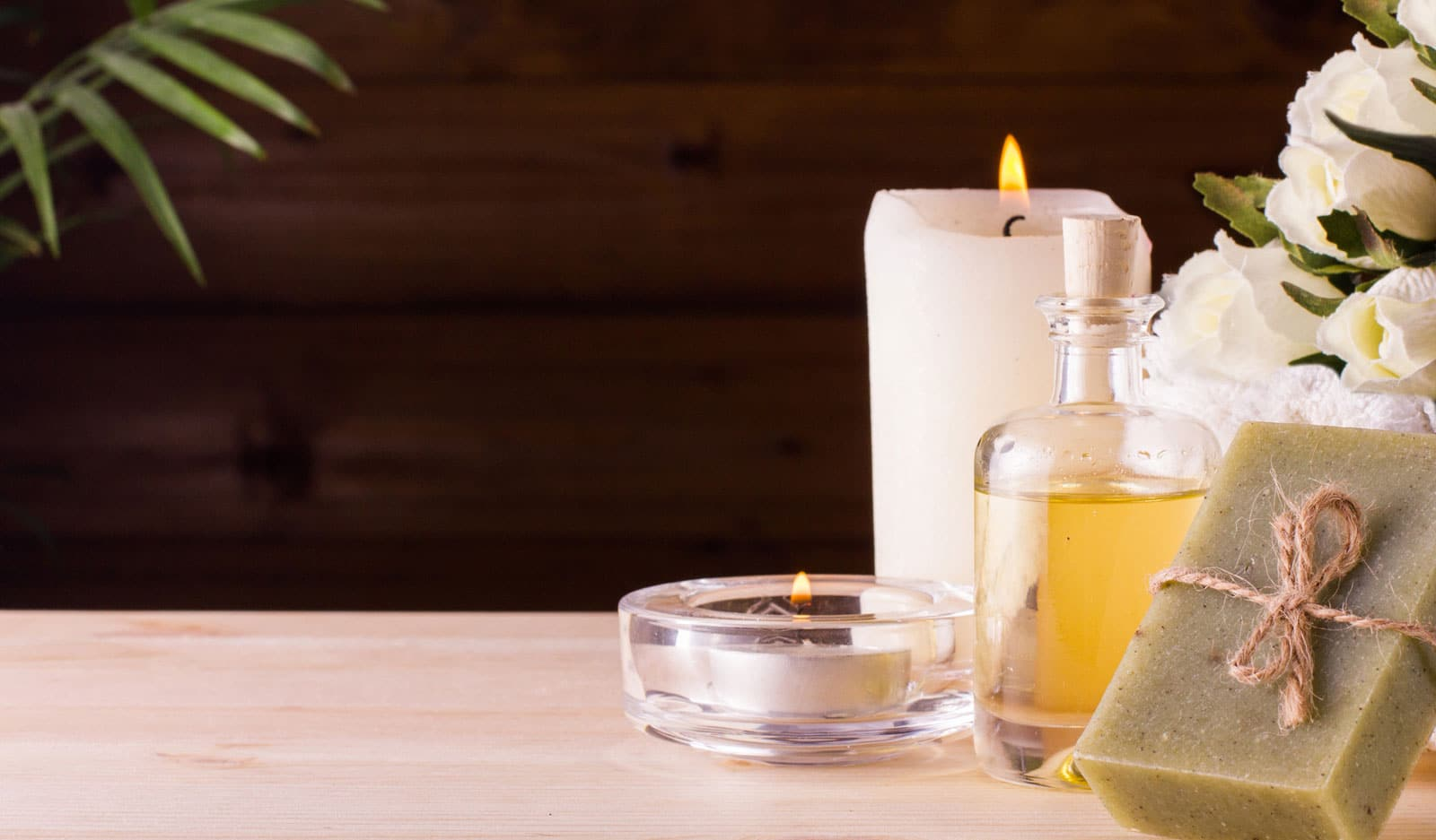A table with a candle, herbal soap a flower and a Essential oil