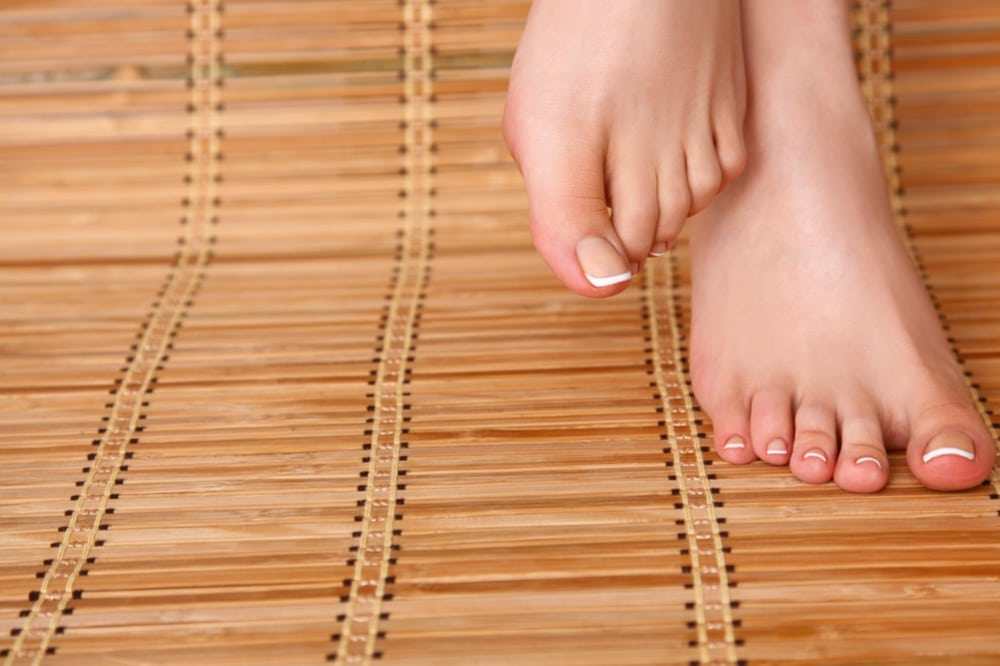 A woman's feet placed on a bamboo rolling mat