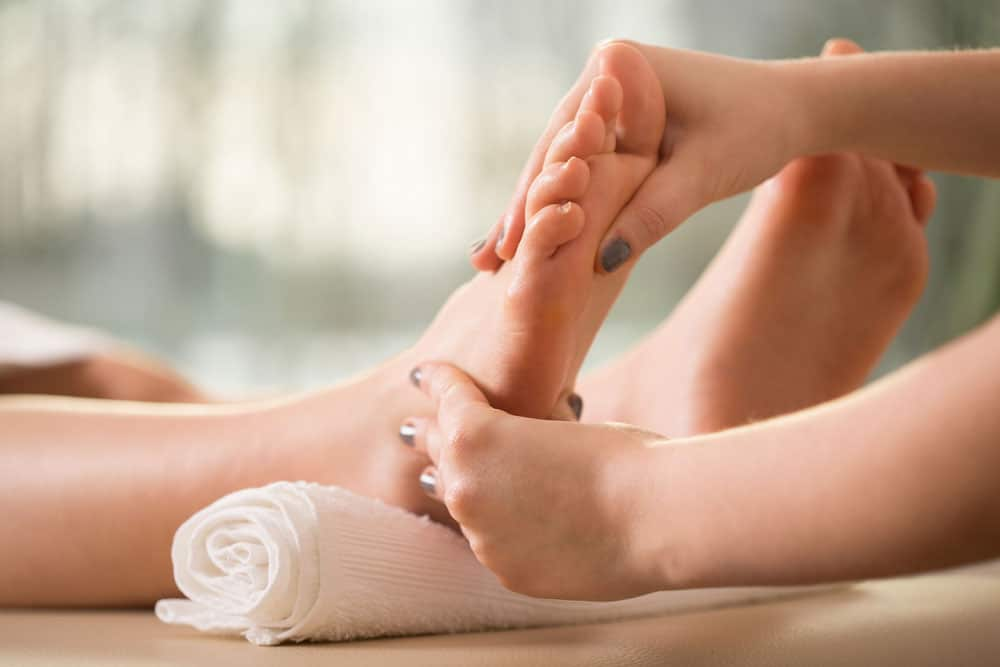 A massage therapist doing a reflexology massage on the right foot of a lady