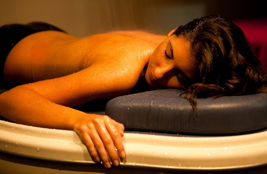 A woman having a good time laying in a table of a Vichy shower