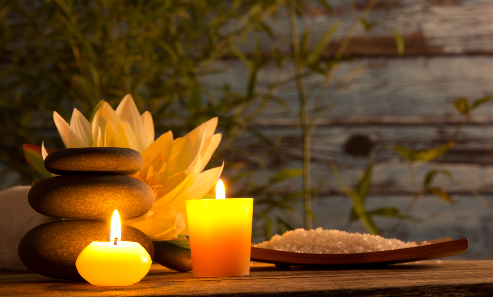 A table with a candle light a plate of salt , herbal flower, stone and a towel